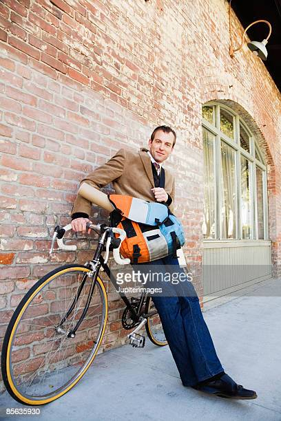 Man with bicycle leaning against brick wall