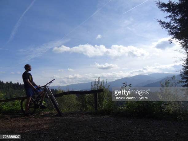 Man With Bicycle On Cliff Against Sky