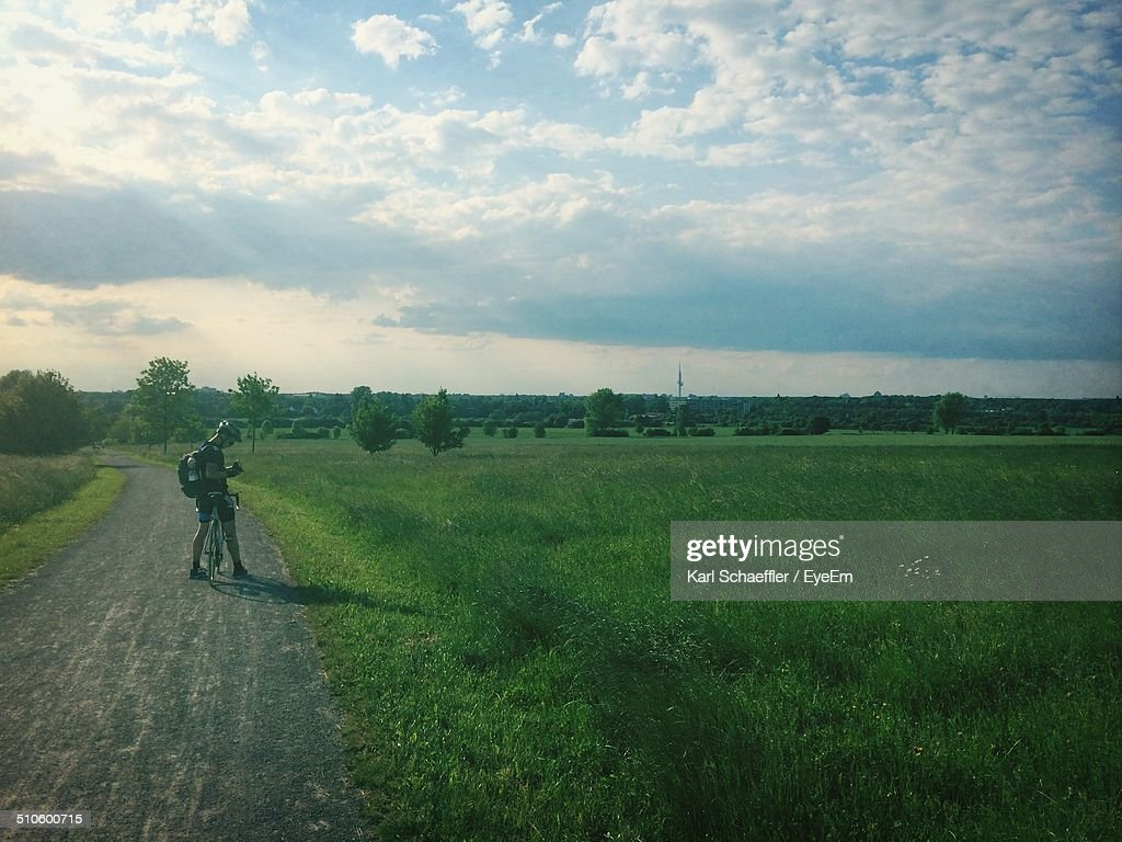 Man with bicycle on country road