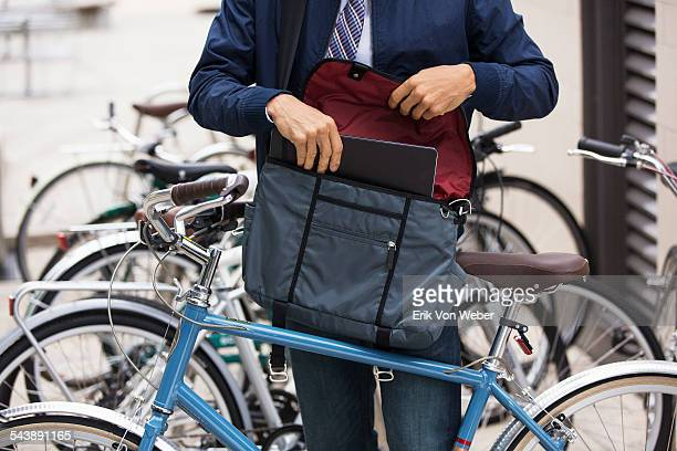 man with bicycle putting laptop into courier bag