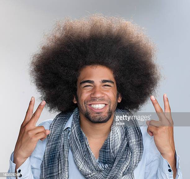 man with big afro hair making peace sign