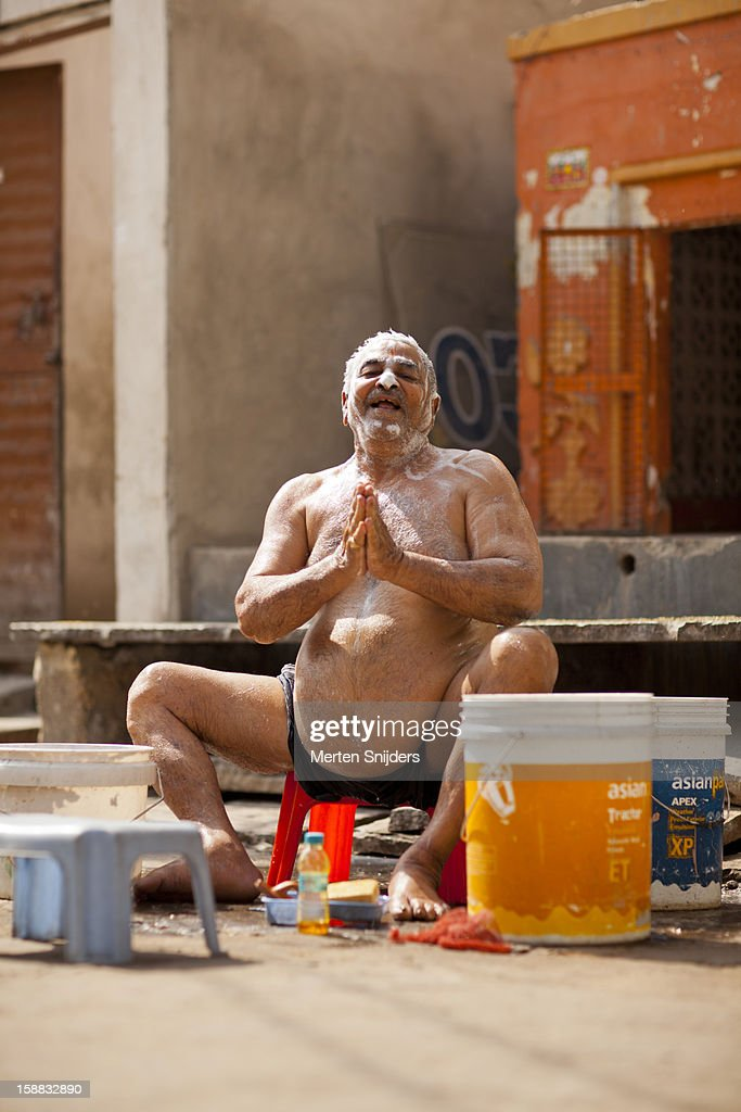 Man with big belly showers from a bucket : Stock Photo