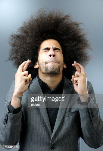 man with big hair keeping fingers crossed