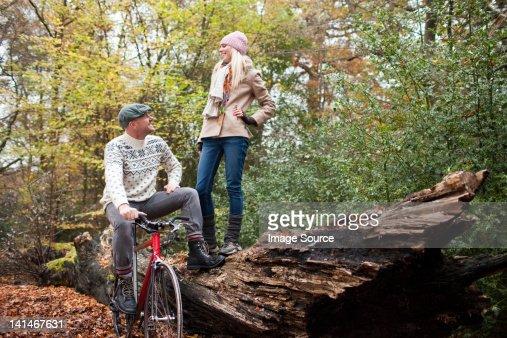 Man with bike and woman standing on log