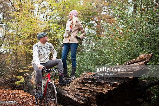 Man with bike and woman standing on log