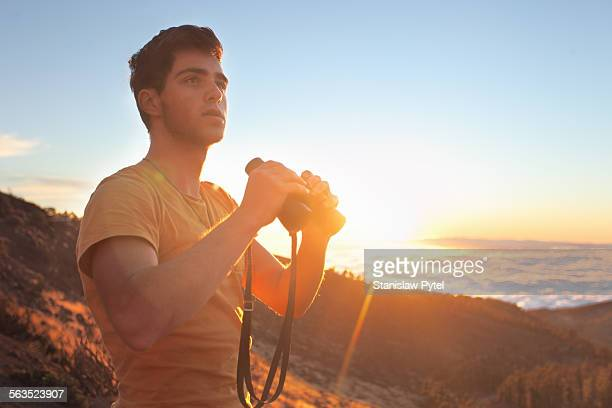 Man with binoculars at sunset in mountains