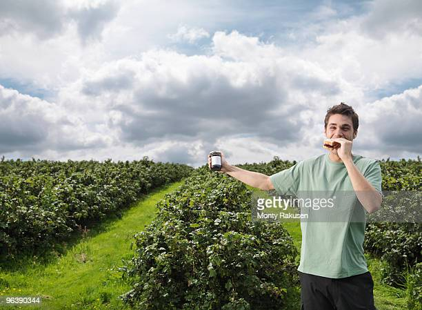 Man With Blackcurrant Sandwich In Field