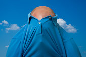 Man with blue shirt over his head