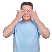 Man with blue t-shirt covering his eyes two hands over white background