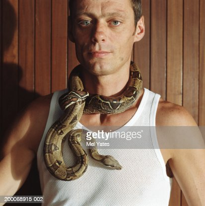 Man with boa constrictor around neck, portrait