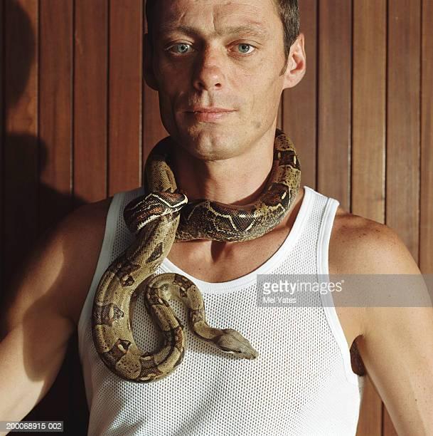 Man with boa constrictor around neck, portrait