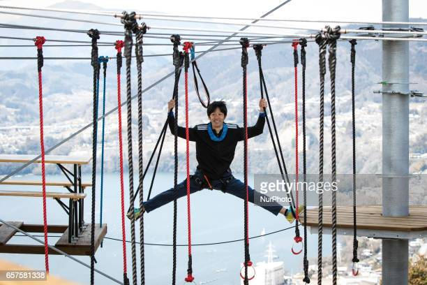 A man with body harness pose like Ninja as he try on the newly open athletic climbing attraction in Sagamiko Resort Pleasure Forest in Kanagawa...
