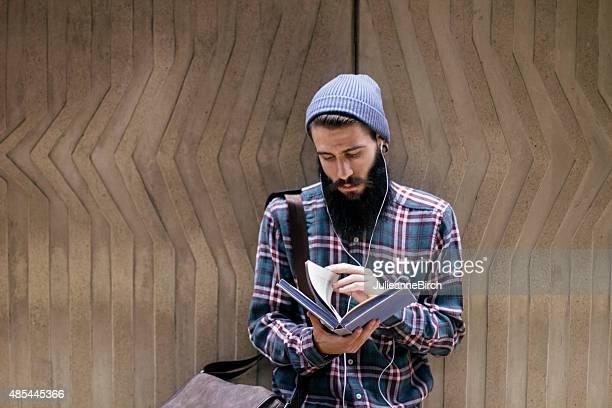 Mann mit Buch und Kopfhörer
