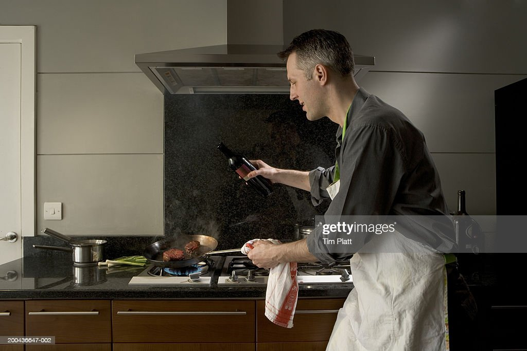 Man with bottle of wine tilting pan on stove, side view : Stock Photo