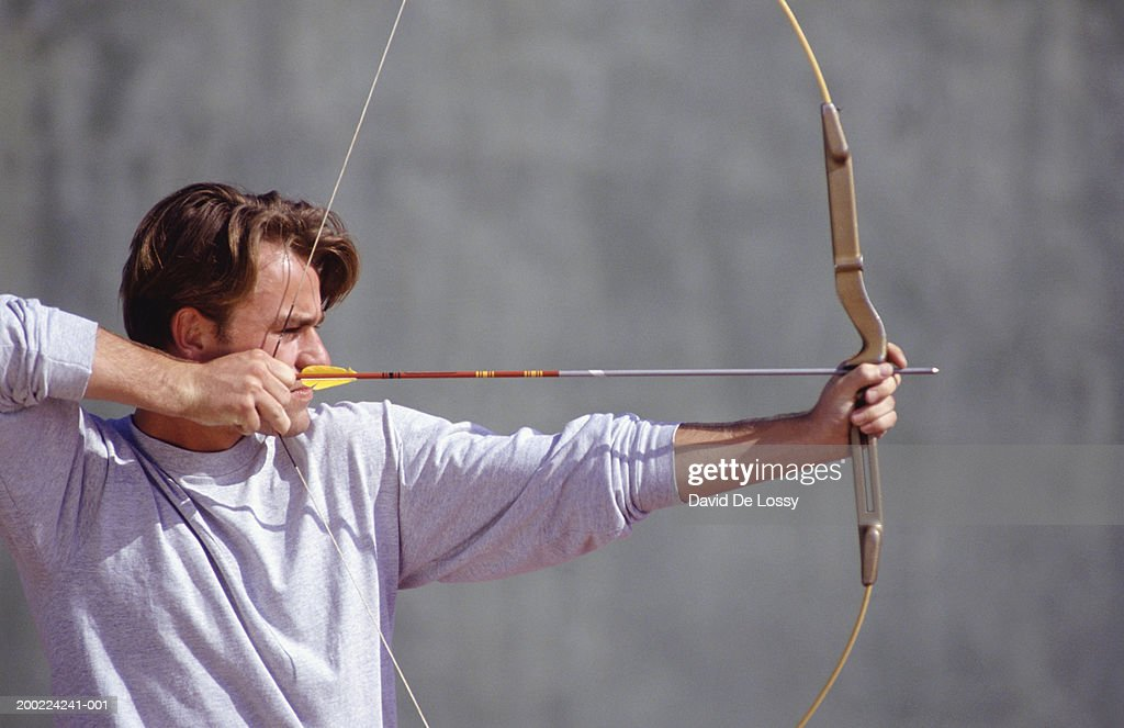 Man with bow and arrow, aiming, side view