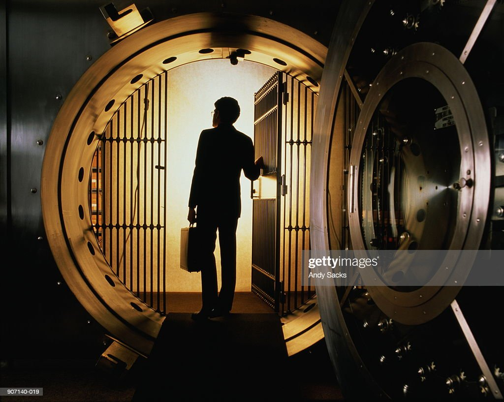 Man with briefcase silhouetted in open door of bank vault