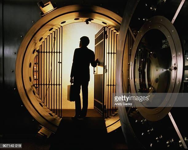 Man with briefcase silhouetted in open door of bank vault
