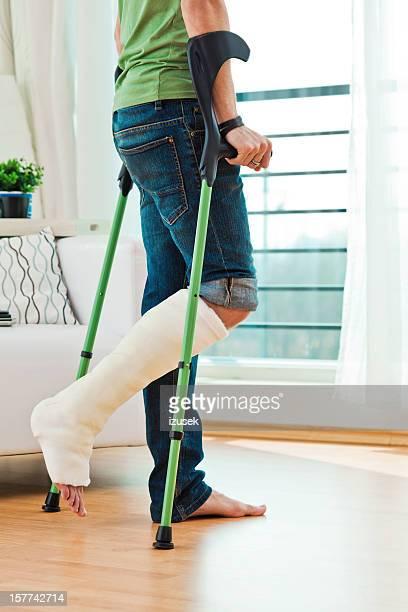 Homme avec une jambe cassée à la maison