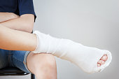 Man with broken leg in a plaster sits on chair white background
