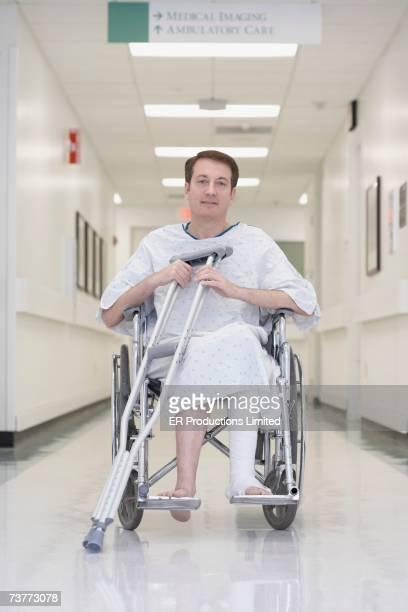 Man with broken leg in wheelchair at hospital