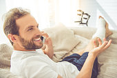 Handsome man with broken leg is talking on the mobile phone and smiling while sitting on couch at home