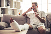 Handsome mature man with broken leg in gypsum is talking on the mobile phone, showing middle finger and laughing while sitting on sofa at home