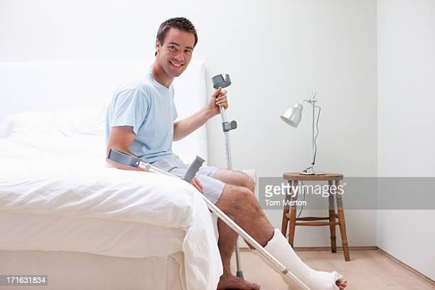 Homme avec une jambe cassée assis sur le lit