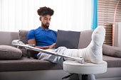 Man With Broken Leg Sitting On Sofa Using Laptop