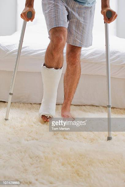 Man with broken leg walking on crutches