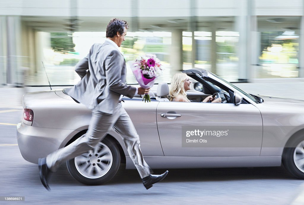 Man with bunch of flowers chasing woman in car : Stock Photo