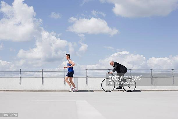 man with bycicle chasing jogger