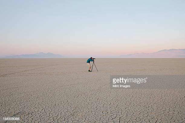 Mann mit Kamera und Stativ auf dem Flachbildfernseher oder saltpan