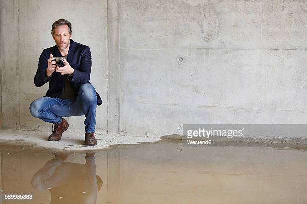 Man with camera on construction site in unfinished building
