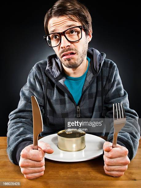 Man with canned food on plate is making faces, humorously