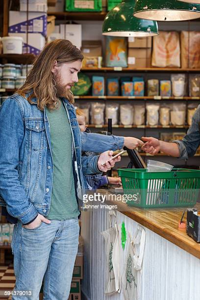 Man with cell phone in shop