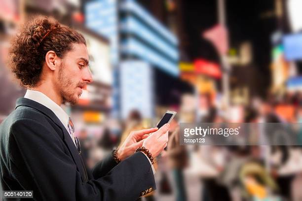 Man with cell phone in Times Square, New York City.