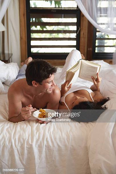 Man with cereal looking at woman with book in bed, close-up