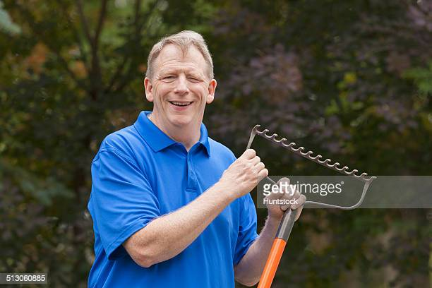Man with Cerebral Palsy and dyslexia holding his rake