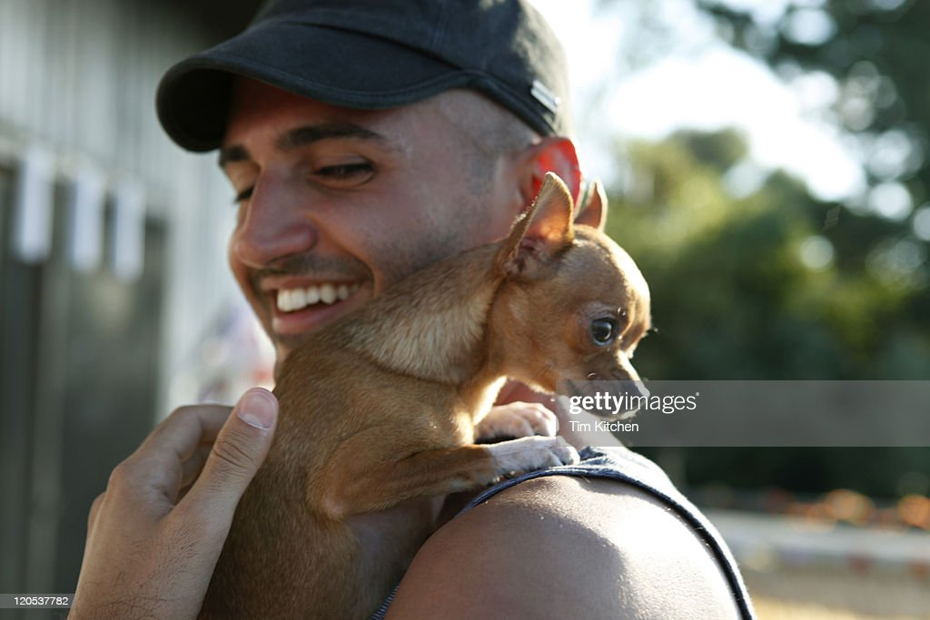 Man with chihuaha on shoulder, smiling : Stock Photo