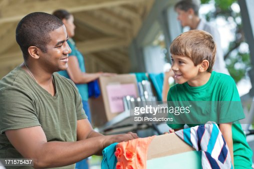 Man with child volunteering at clothes and food donation place