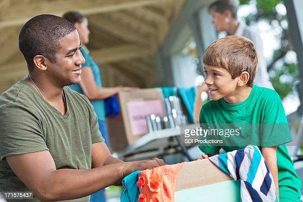 Mann mit Kind ehrenamtliche Tätigkeiten bei Kleidung und Essen Spende place