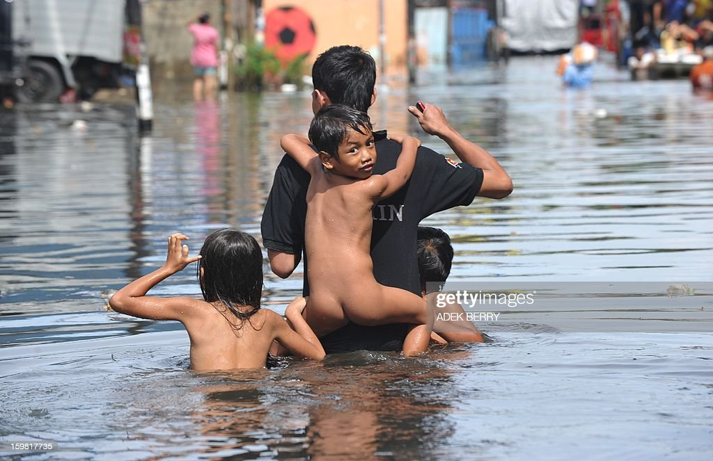 A man with children wades through a flooded street in Jakarta on January 21, 2013. Companies and consumers have started to calculate damages and losses from the widespread floods that hit Jakarta on, claiming at least 15 lives a police spokesman said on January 19, displacing thousands from their homes and afflicting capital residents with water-borne illnesses, a local newspaper reported.