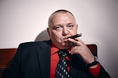 Portrait of serious middle aged businessman wearing black suit, red shirt and wristwatch sitting on old fashioned sofa in office and smoking cigar