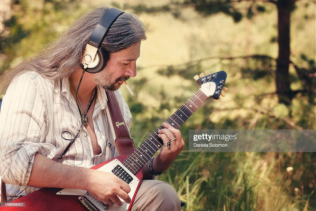 Man with cigarette playing on electric guitar : Stock Photo