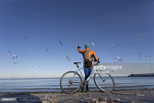 Man with city bike feeding seagulls