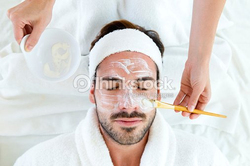 Man with clay facial mask in beauty spa. : Stock Photo
