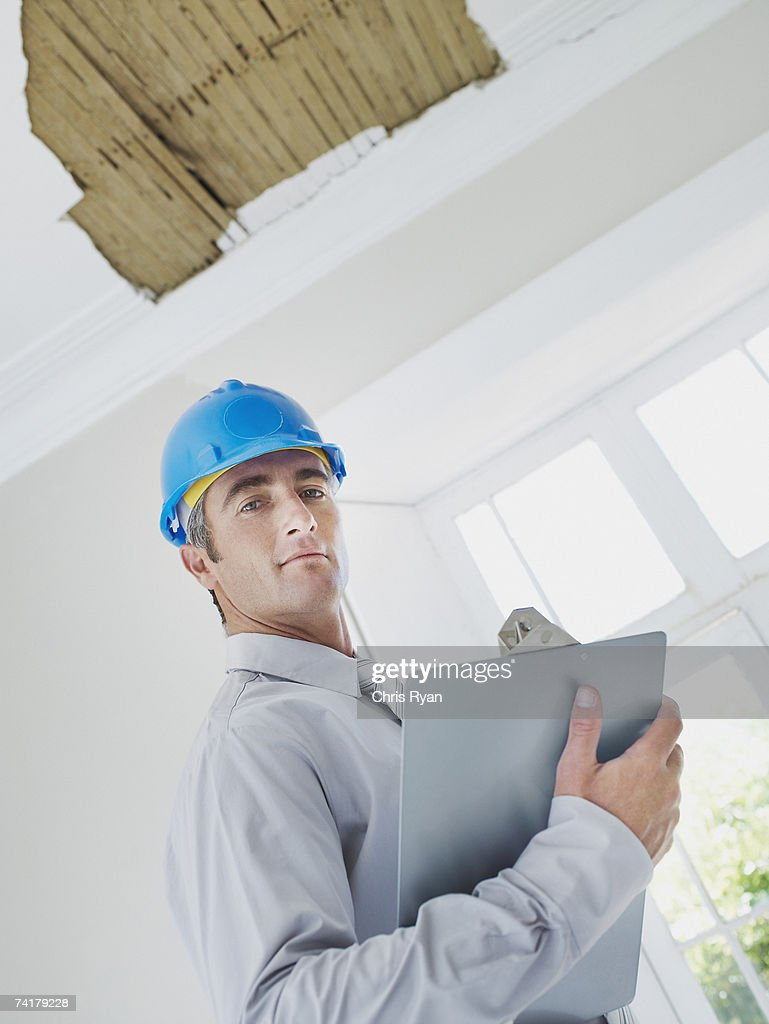 Man with clipboard and helmet in house with damaged ceiling : Stock Photo