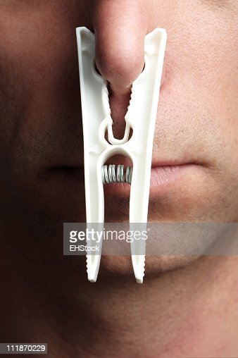 Man with Clothes Pin on Nose Close Up