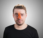 Portrait of caucasian man with orange clothespin on his nose - bad smell concept photography.