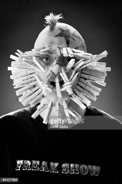 Man with clothing pins on face.